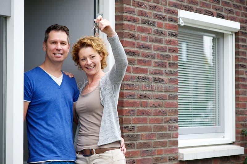 Accoppi sorridere e la tenuta delle chiavi alla loro nuova casa fotografia stock libera da diritti
