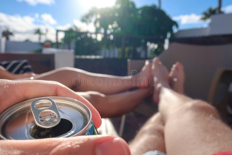 Accoppi su una vacanza estiva si siede al sole e beve la birra fotografia stock