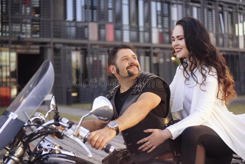 Accoppi sui precedenti dell'ufficio su un motociclo Il tipo ha portato la sua amica lavorare Ragazza in un vestito bianco lungo s fotografie stock libere da diritti