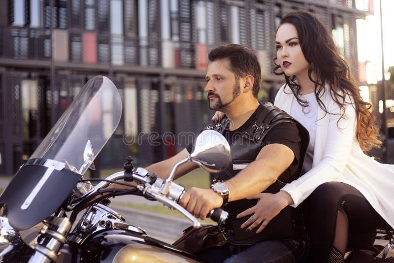 Accoppi sui precedenti dell'ufficio su un motociclo Il tipo ha portato la sua amica lavorare Ragazza in un vestito bianco lungo s fotografia stock