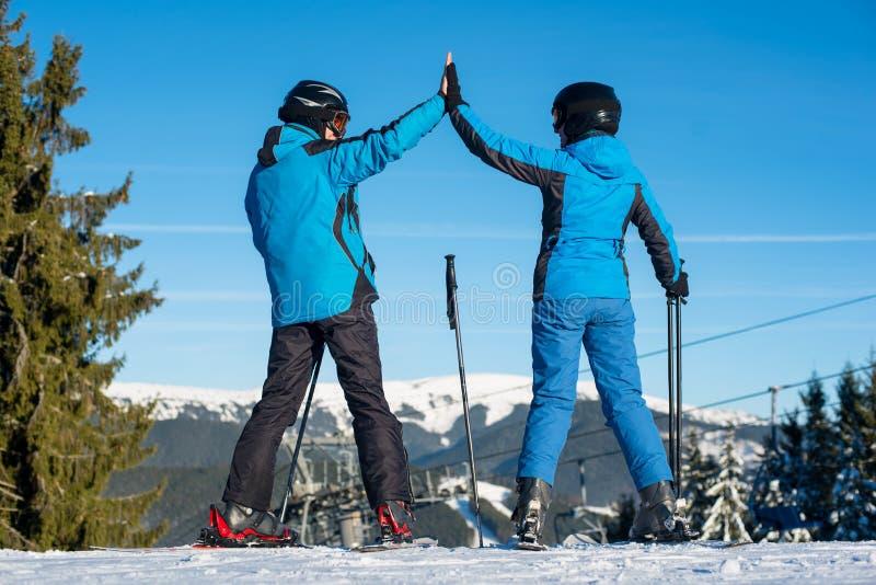 Accoppi tenersi per mano stare con gli sci sulla cima della montagna immagini stock