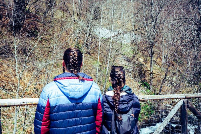 Accoppi in un ponte che guarda il fiume negli amanti della foresta da dietro con la treccia fotografia stock libera da diritti