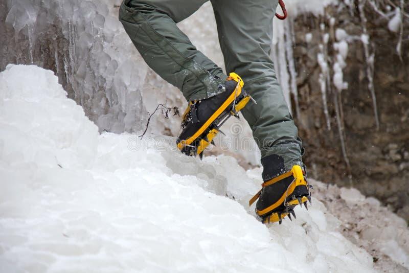 Accoppiamenti dei caricamenti del sistema dell'alpinista in crampons fotografia stock
