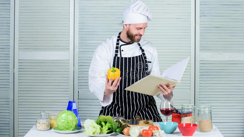 According to recipe. Man bearded chef cooking food. Guy read book recipes. Culinary arts concept. Man learn recipe. Improve cooking skill. Ultimate cooking stock photos