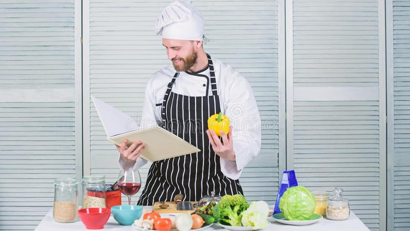 According to recipe. Man bearded chef cooking food. Guy read book recipes. Culinary arts concept. Man learn recipe. Improve cooking skill. Ultimate cooking royalty free stock images