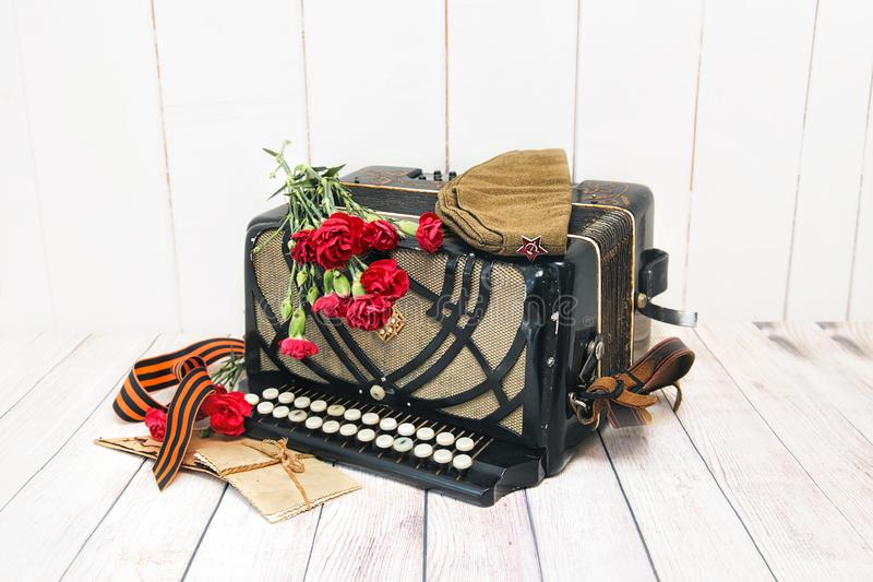 Accordion, red carnations, soldier's cap, St. George ribbon and old letters royalty free stock photos
