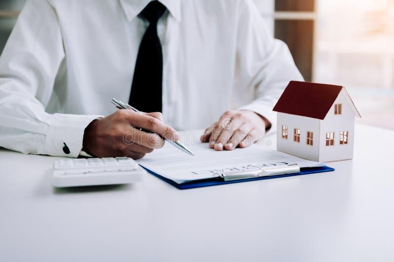 Accordo di contratto di firma della carta dell'uomo asiatico per la casa con la casa di modello immagini stock