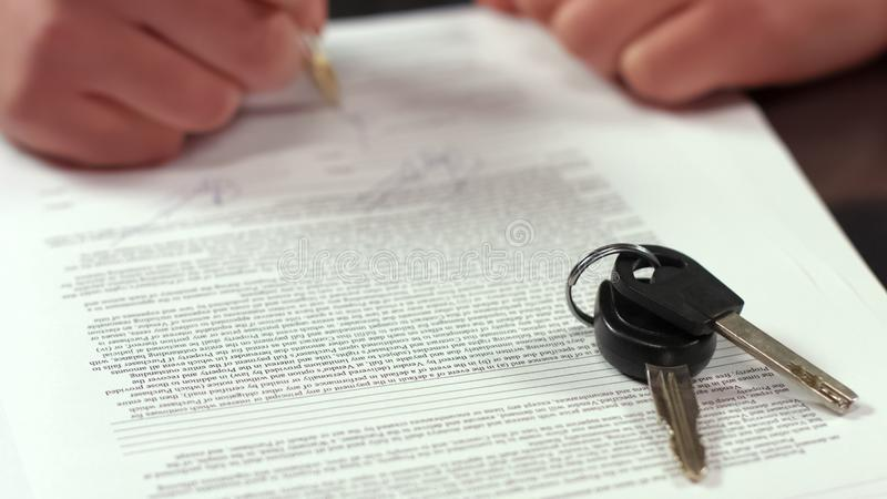 Accordo di firma di affitto della mano del compratore, chiavi sul primo piano della tavola, assicurazione di trasporto immagini stock libere da diritti