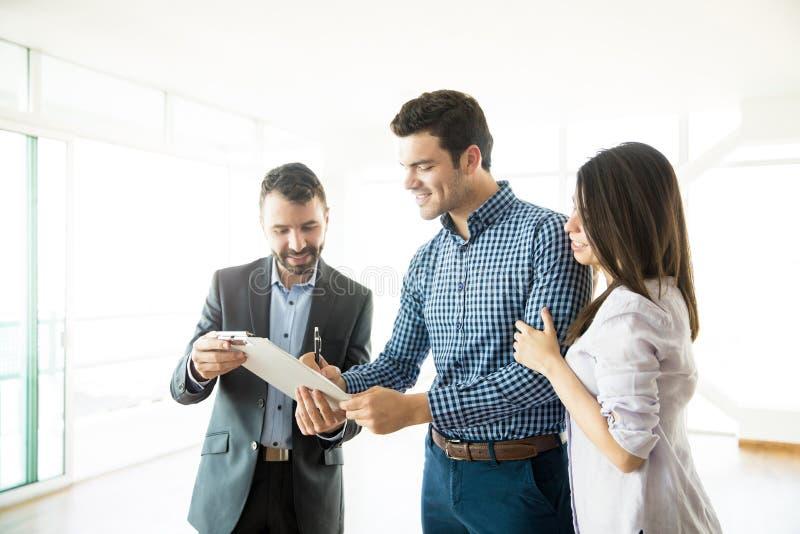 Accordo di firma delle coppie dall'agente immobiliare In New Apartment immagine stock libera da diritti