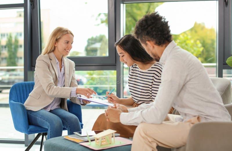 Accordo di firma di mutuo ipotecario della donna asiatica in ufficio dell'agente immobiliare immagine stock