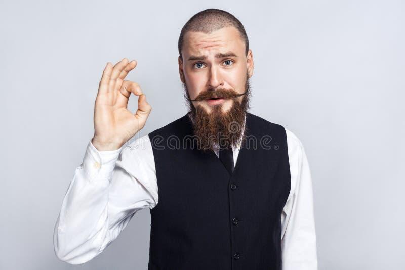 accosenta Uomo d'affari bello con i baffi del manubrio e della barba che esaminano macchina fotografica con il segno giusto fotografia stock