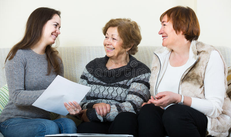 Account manager helping women with finances at home. Happy spanish account manager helping elderly women with finances at home stock photo