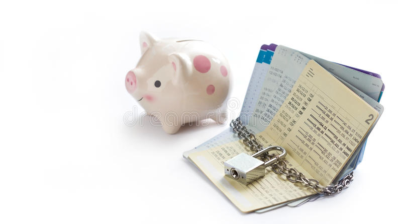 Account passbooks were locked by chain and key with piggy bank on white background royalty free stock image