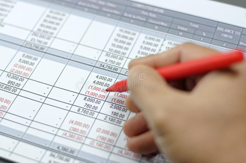 Account Report. Close up of Accountant hand checking report with narrow depth of field stock images