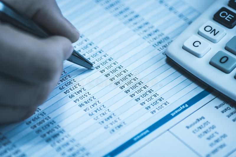 Accountant in accounting. Spreadsheet with human hand holding pen and calculator in business blue. Stock balance sheet royalty free stock photo