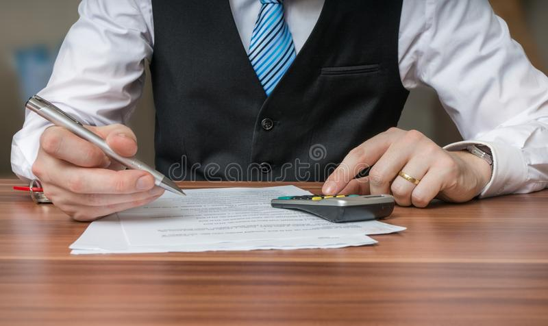 Accountant or business man is calculating taxes with calculator stock photo