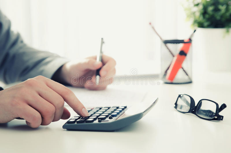Accountant calculates tax. Working in the office with calculator royalty free stock photos