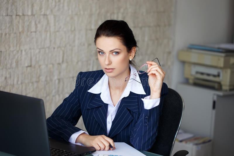 Accountant calculating taxes in office. Taking off glasses stock photography