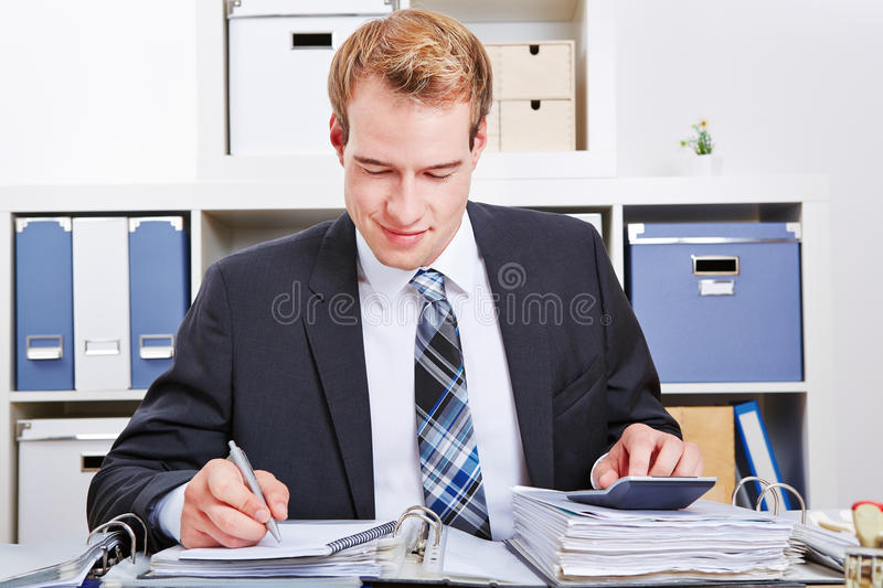 Accountant doing financing. In the office with a calculator for a tax audit royalty free stock image