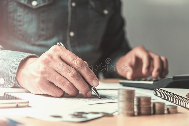 accountant using pen and calculator working with document in off stock photo