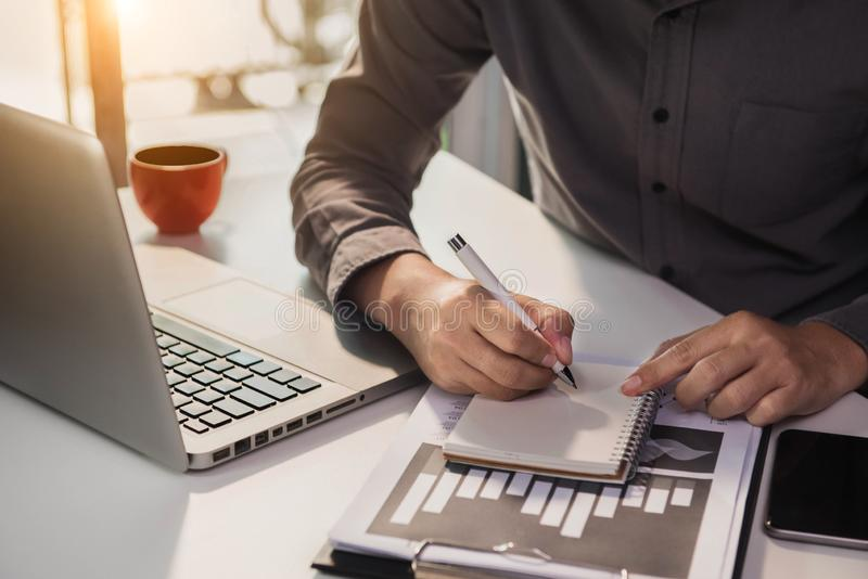 Accountant working on laptop computer with business document, graph diagram and calculator on office table in office. stock photos