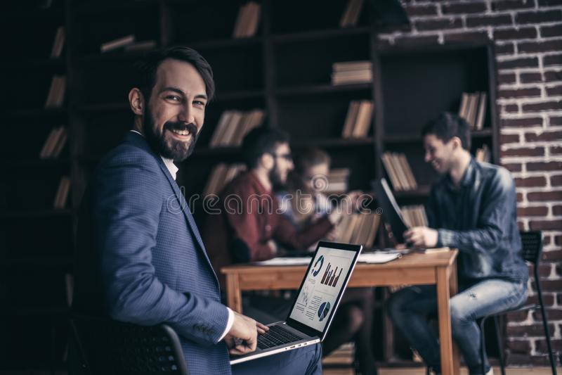 Accountant works with financial charts on the laptop in the offi stock photography