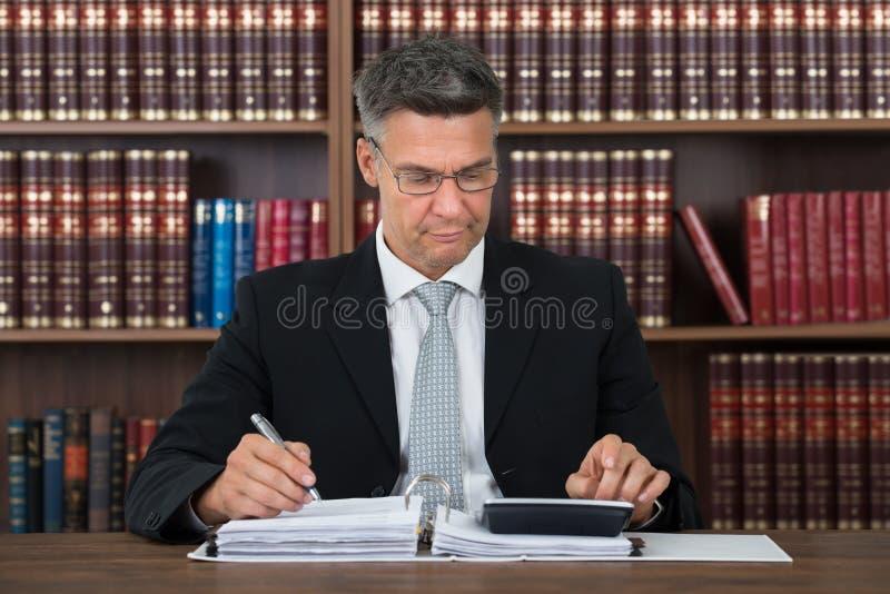 Accountant Writing On Document terwijl het Gebruiken van Calculator bij Lijst royalty-vrije stock foto's
