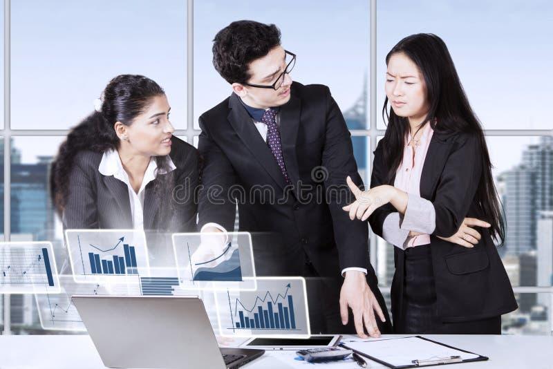 Accountants die financiële grafiek in bureau spreken stock foto's
