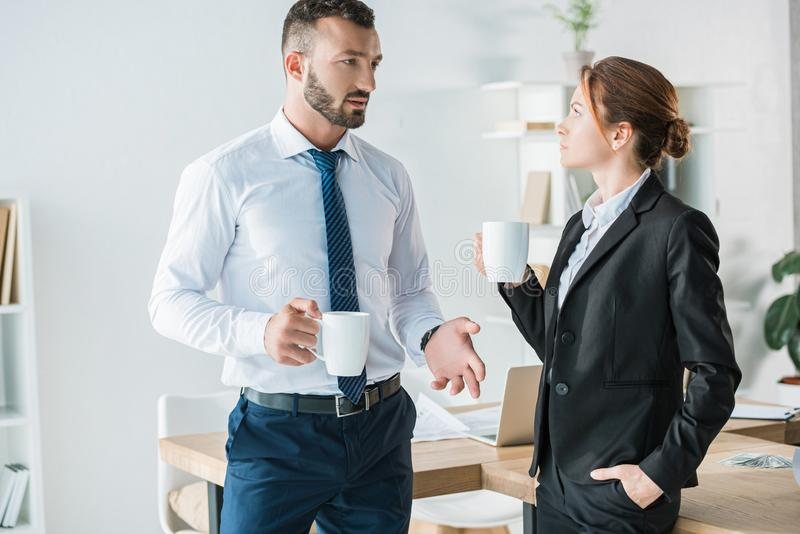 Accountants talking in office during. Coffee break stock image