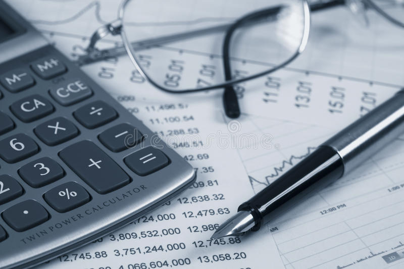 Accounting. A calculator, reading glasses and pen on top of financial reports stock photos