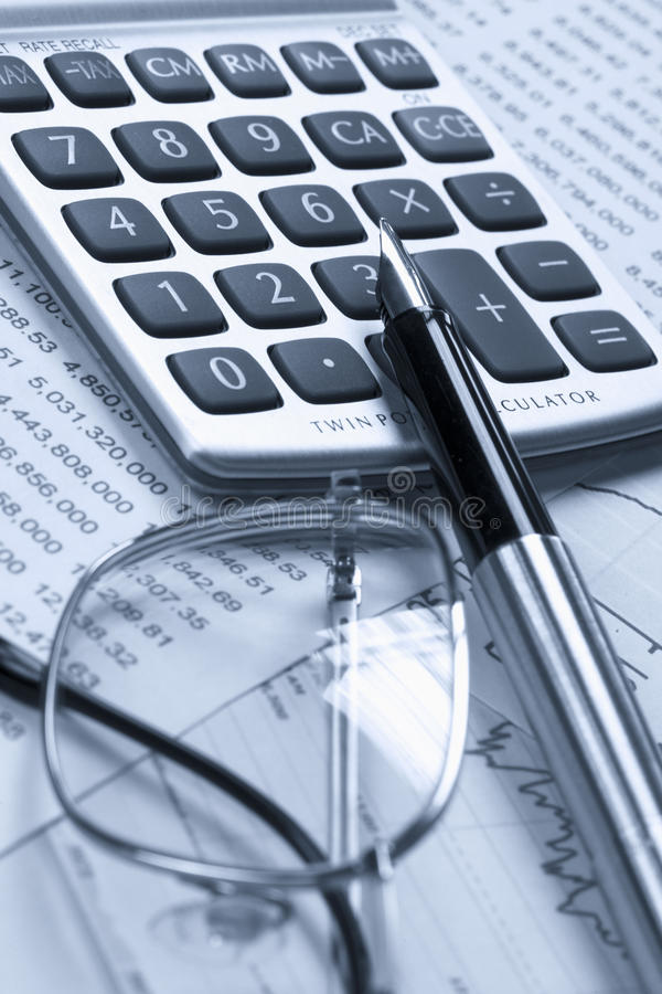 Accounting. A calculator, reading glasses and pen on top of financial reports royalty free stock photo