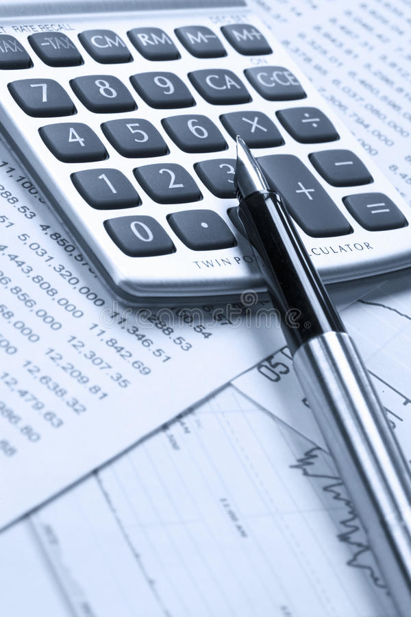 Accounting. A calculator and pen on top of financial reports royalty free stock photo