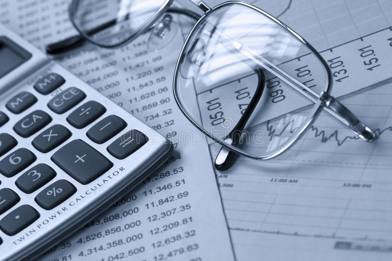 Accounting. A calculator, reading glasses on top of financial reports stock photo