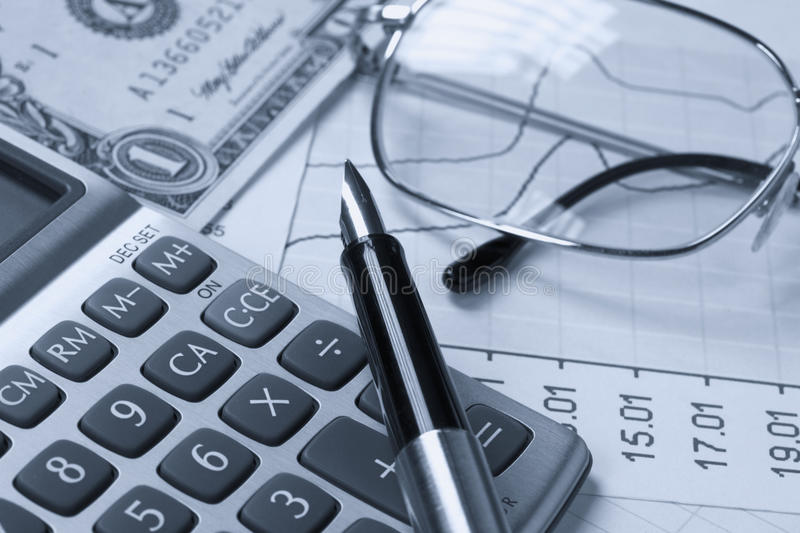 Accounting. A calculator, reading glasses and pen on top of financial reports royalty free stock photography