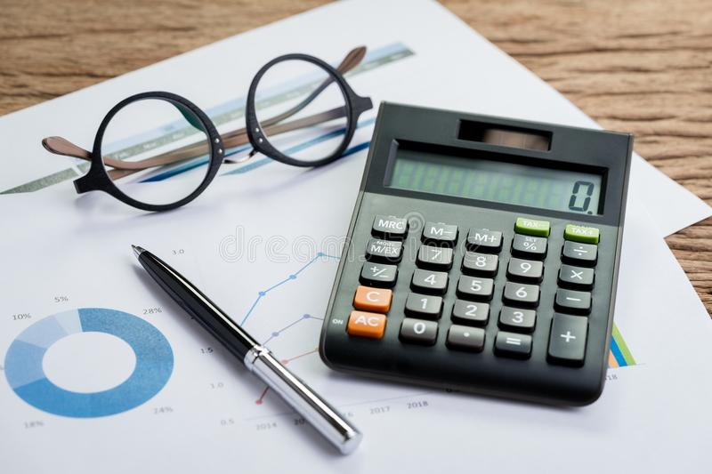 Accounting equipments, work corporate profit or finance calculations, savings concept with pen, calculator and eyeglasses on stock photo