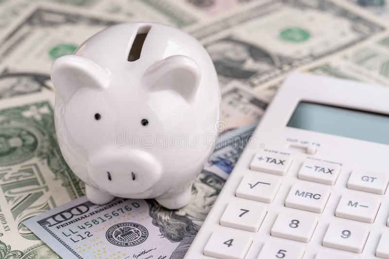Accounting, finanacial investment or budget concept, cute white piggy bank or coin bank and calculator on pile of US America. Dollar banknotes money stock images