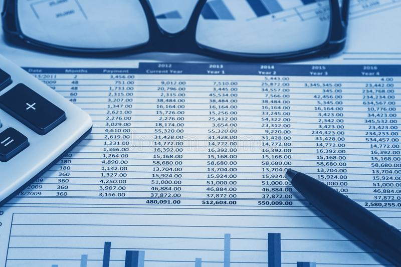 Accounting financial bank banking account stock spreadsheet data for accountant with glasses pen and calculator in blue analysis royalty free stock photo