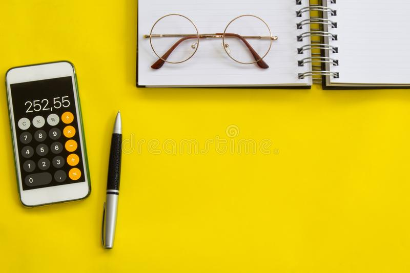 Accounting, financial concept, flat lay or top view of pen, smart phone with calculator with white notepad on vivid yellow backgro stock photo