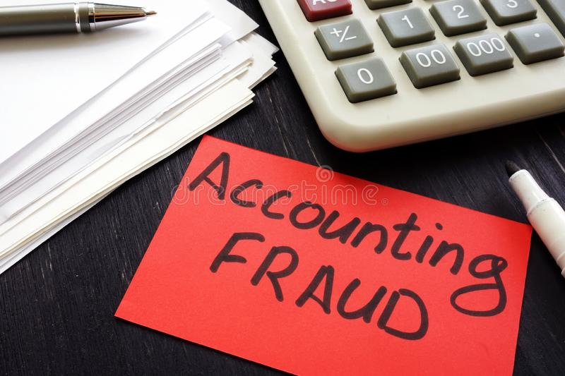 Accounting fraud inscription and audit report. Accounting fraud inscription and audit report on desk royalty free stock photo
