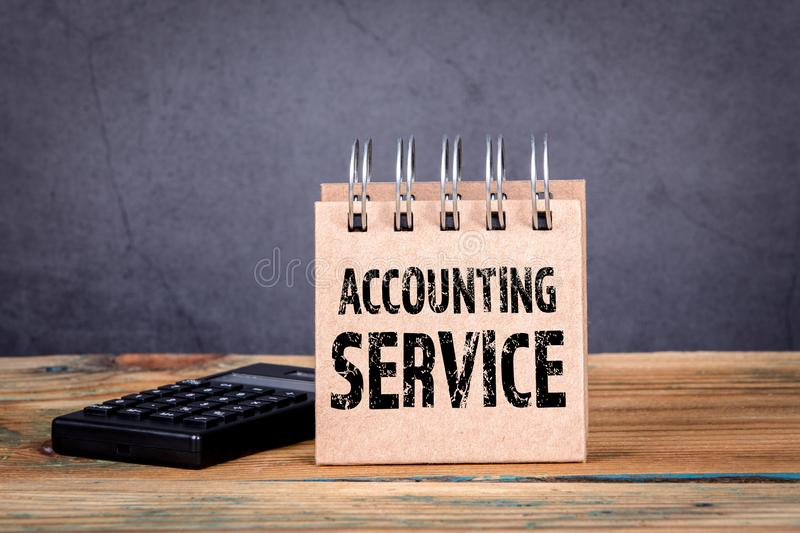 Accounting Service. Calculator and notebook. On a wooden table stock photos
