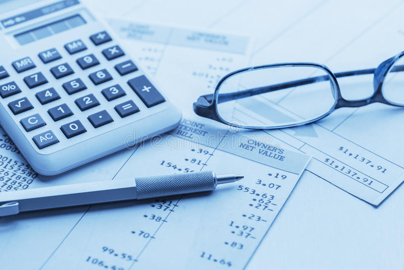 Accounting. Work space with calculator, glasses, pen and profit and loss statements stock photos