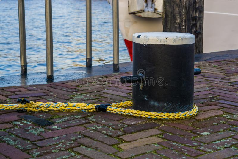 Accouplement du poteau avec une corde pour fixer le bateau, équipement au port, fond de transport de l'eau photo stock
