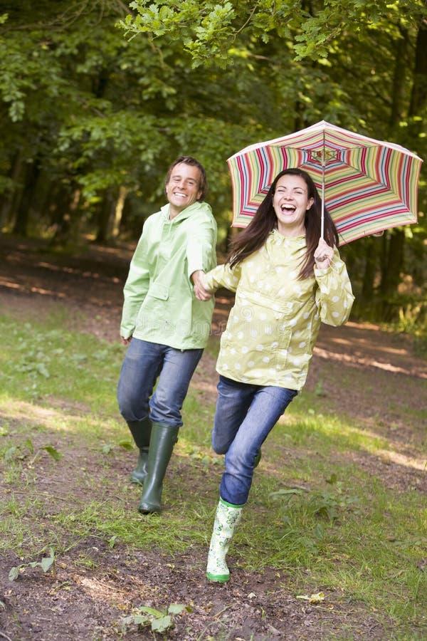 Accouplez à l'extérieur l'exécution avec le sourire de parapluie photos stock