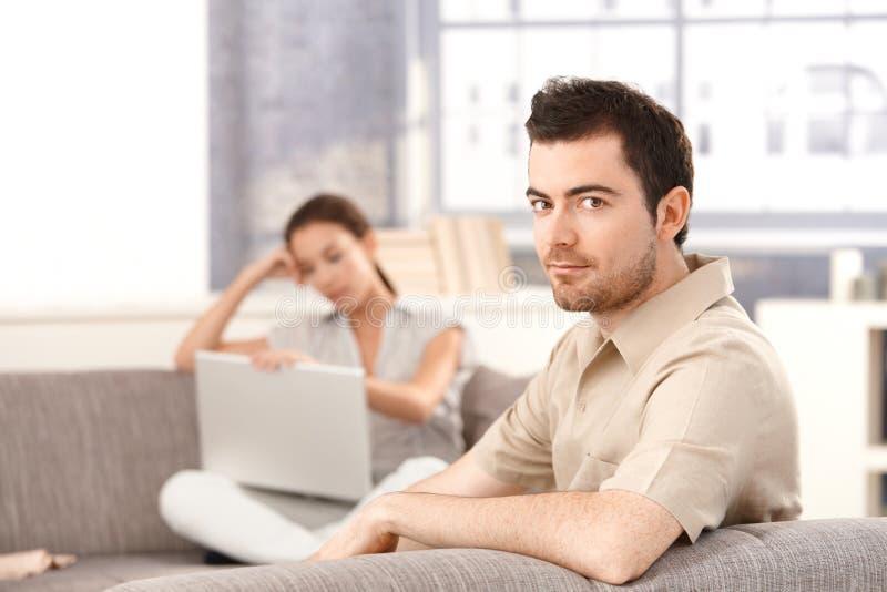 accouplez donner l'homme à la maison que le rouge s'est levé sofa de sourire se reposant aux jeunes de femme photo stock