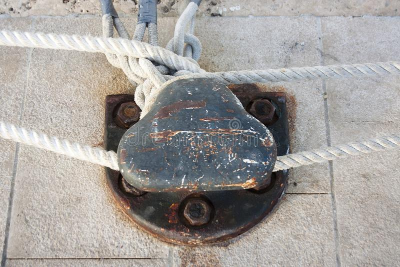 Accouplez la borne sur le pilier en pierre avec des cordes de bateau image libre de droits