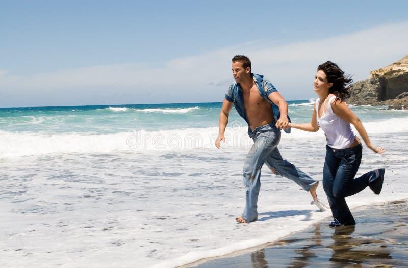Accouplez le fonctionnement par le bord de la mer dans la plage image libre de droits