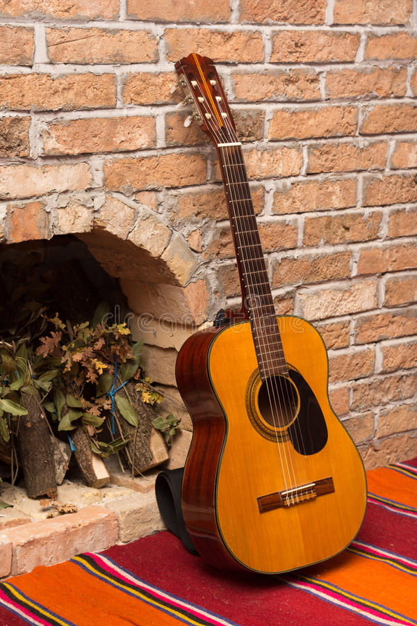 Accoustic guitar on the brick wall.  royalty free stock image