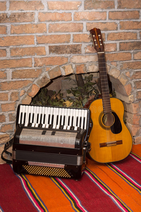 Accoustic guitar on the brick wall and accordion.  royalty free stock photos