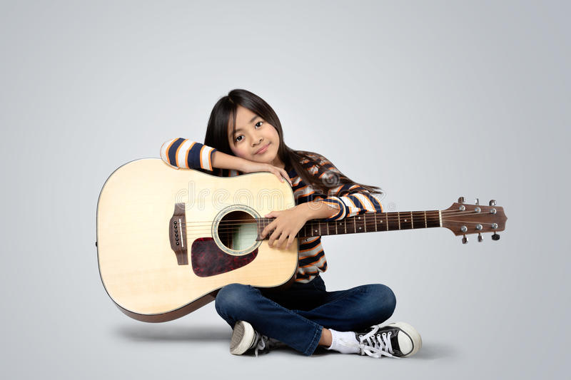 Accoustic guitar. Young asian girl with a accoustic guitar, Isolated on grey background stock photo