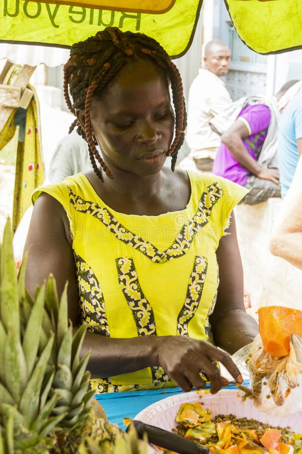 African woman in ghana. Accra, Ghana - December 31, 2016: African happy woman with a fruit in a market in Accra, Ghana stock photos